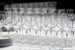 Win szkła z talerzami na stole Czarny tło Zdjęcia Stock