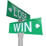Win Vs Lose Two Way Street Road Sign Direction Arrows. Win Vs Lose on green two-way road or street signs to illustrate a turning point where you must choose a Stock Photo