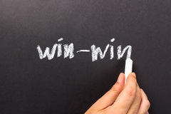 Win-win. Hand writing Win-win on chalkboard Stock Photo