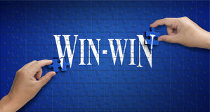 Win win word on Jigsaw puzzle. Man hand holding a blue puzzle to Royalty Free Stock Photography