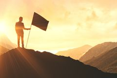 Win and winner concept. Businessman with flag standing on abstract mountain top. Win and leadership concept Royalty Free Stock Photo