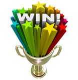 Win Word in Trophy - Burst of Stars Fireworks. A golden first place trophy with the word Win and colored star fireworks blasting out of it, illustrating the Stock Image