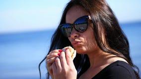 (wina) Lato, outdoors portret piękna brunetki kobieta z długim ciemnym włosy, jest ubranym okulary przeciwsłonecznych, z apetite  zbiory wideo