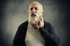 Winced senior man over dark Royalty Free Stock Images
