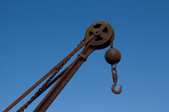 Winch and hook. A vintage winch and hook made of rusty metal with a wheel and chain against a blue sky Stock Photo
