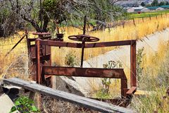 Winch of pair of rusty antique irrigation ditch gates against sky with tall grass in Heber City, Utah along the back side of the W royalty free stock photos