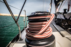 Winch with red and white rope on sailing boat in the sea Royalty Free Stock Image