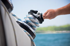 Winch and sailors hands on a sailboat Stock Image