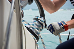 Winch and sailors hands on a sailboat Royalty Free Stock Image