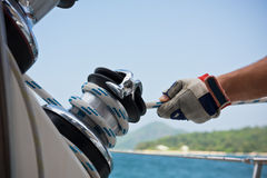 Winch and sailors hands on a sailboat Stock Photos
