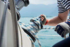 Winch and sailors hands on a sailboat Stock Photography