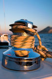 Winch on the yacht. Rope rolled up on a winch in a yacht during sunset Royalty Free Stock Images
