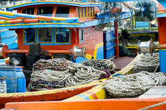 Winches and coiled ropes on colorful fishing  boats moored next to each other Stock Photos
