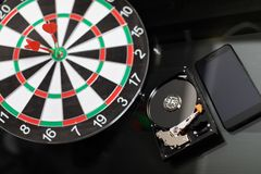 Winchester with mobile phone and Darts at targets on dark background. The idea of business. Hard drive and mobile phone with blank screen lie on table next to royalty free stock image