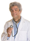 Wincing Doctor. Isolated wincing mature medical doctor using stethoscope Stock Photography
