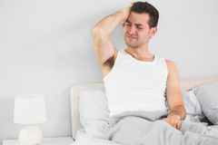 Wincing handsome man having a headache. In bright bedroom Royalty Free Stock Photography