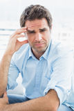 Wincing man with headache sitting on the couch looking at camera Stock Photography