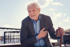 Senior man suffering from severe angina. Wincing in pain. White-haired elderly man holding a cane and touching his chest because of suffering from angina Royalty Free Stock Photo