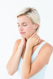 Wincing woman suffering from neck ache. On white background Stock Photos