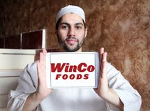 WinCo Foods logo. Logo of WinCo Foods on samsung tablet holded by arab muslim man. WinCo Foods, Inc. is a privately held, majority employee-owned American Royalty Free Stock Image