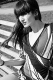 On wind. Black and white portrait of pretty brunette female fashion model with long and thick fringe and with wind in her hair sitting on bench on a bright sunny Stock Photography