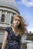 In the wind. Young woman in the wind in front of the dome, Saint-Petersburg Stock Photography