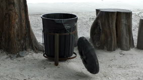 The wind batters a trash bin hanging out on seacoast stock video