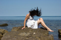 The wind is biting a girl hair. A girl sitting on a stone by the sea. The wind is biting her hair stock photos