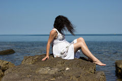 The wind is biting a girl hair. A girl sitting on a stone by the sea. The wind is biting her hair stock photo