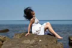 The wind is biting a girl hair. A girl sitting on a stone by the sea. The wind is biting her hair royalty free stock photos