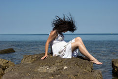 The wind is biting a girl hair. A girl sitting on a stone by the sea. The wind is biting her hair royalty free stock photography