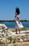 The wind is biting a girl hair. A girl standing on stones by the sea. The wind is biting her hair stock images