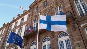 Wind blowing Finland and EU flags on the mast against blue sky background in front of Hôtel de Ville de Strasbourg, France.