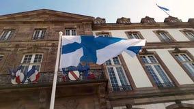 Wind blowing Finland flag on the mast against blue sky background in front of Hôtel de Ville de Strasbourg, France. stock video footage