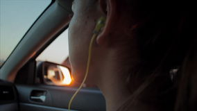 Wind Blowing Through Girl's silhouette and Hair In a car. Girl teen listening to music in the car. Sunset stock video footage