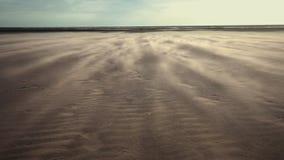 Wind blowing sand over barren dunes. Sandstorm over empty sand dunes with sea in background. Vast barren wasteland scape stock video footage