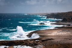 Wind blowing the water and waves against the rocks on the beautiful coast.  stock photo