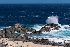 Wind blowing the water and waves against the rocks on the beautiful coast.  royalty free stock photos