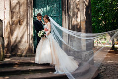 Wind blows bride& x27;s veil while she stands with groom. Before an old green door Royalty Free Stock Photography