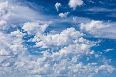 Wind blows lots of clouds over blue sky Stock Photo