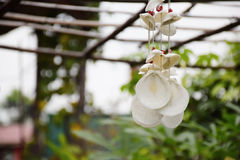 Wind chime made from shells hanging on roof Royalty Free Stock Images