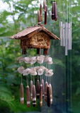 Wind chimes. An old wooden chalet-type wind chime alongside tubular chimes set against a rain-streaked window Stock Photo