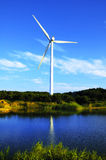 Wind-driven generator. Nearby pond Stock Photos