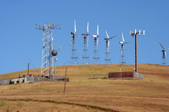 Wind-driven generators & cell site. Several wind-driven generators atop a hill in California, USA, and cell sites Stock Photography