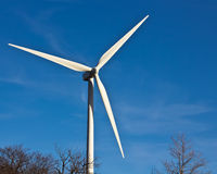 Wind energy. A wind power windmill  turning against a deep blue sky.   Perfect for an article on green or alternative energy Stock Photo