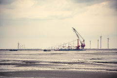 Wind energy constructed at the mud flat Royalty Free Stock Photos