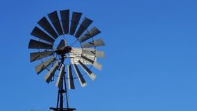 Wind Energy. An old multi-blade wind pump spinning with the blue skies in the background. Wind power is currently the cheapest source of large-scale renewable stock video