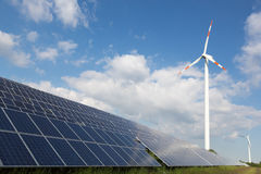 Wind energy turbine with some solar panels for electricity production Royalty Free Stock Photos