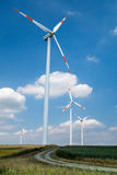 Wind energy turbines. A group of wind energy plants on a field stock image