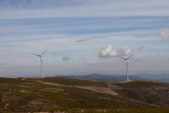 Wind energy turbines. In a landscpae over a beautiful blue sky stock photo